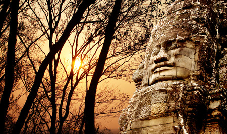 prasat bayon: Giant stone face in Prasat Bayon Temple and trees on sunset sky background. Famous landmark Angkor Wat complex, khmer culture, Siem Reap, Cambodia