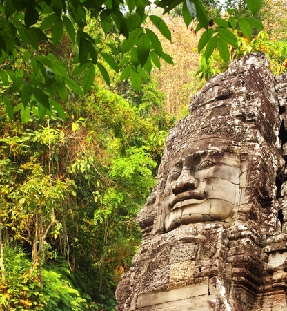prasat bayon: Giant stone face in Prasat Bayon Temple and trees in rainforest. Famous landmark Angkor Wat complex, khmer culture, Siem Reap, Cambodia
