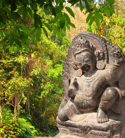 Stone sculpture of dancing hindu god and trees in rainforest Stock Photo