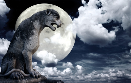 Ancient lion statue and bright moon in the night sky. Stock Photo