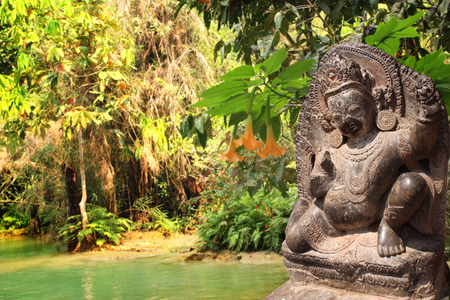 woodland sculpture: Stone sculpture of dancing hindu god and trees in rainforest Stock Photo