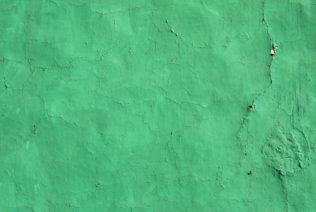 Grunge background with old stucco wall texture with cracked paint of green color