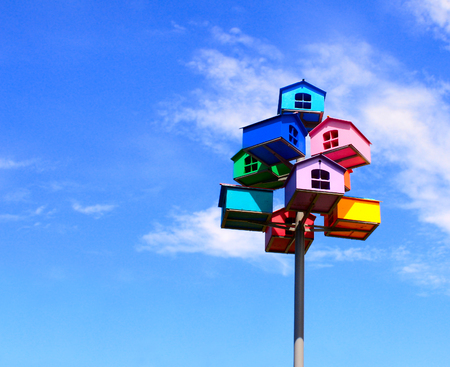 Colorful nesting boxes on blue sky background