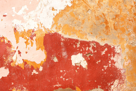 smudge: Grunge background with old stucco wall texture of beige color and cracked paint of red, pink and yellow color