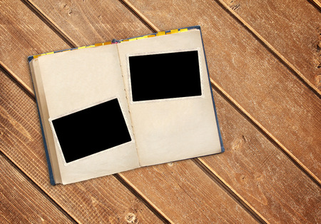 Retro book and vintage photoframes on old wooden planks. Mock up template. Copy space for your text Stockfoto