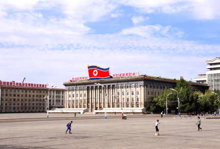 NORTH KOREA, PYONGYANG - SEPTEMBER 26, 2017: Boys ride rollerblading in Kim Il Sung Square near to building of Ministry of Foreign Trade of the DPRK, capital of North Korea Editorial