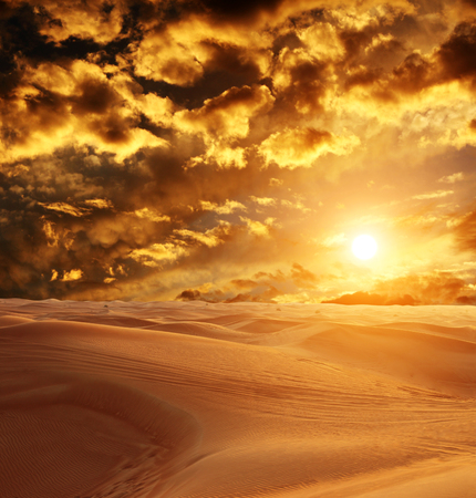 Sunset in desert. Beautiful landscape with sand dunes, cloudy sky and sun Stock Photo
