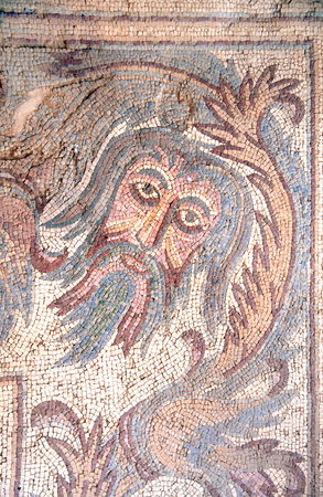 Ancient byzantine natural stone tile mosaics with face of mythical god and floral ornament, Madaba, Jordan 写真素材