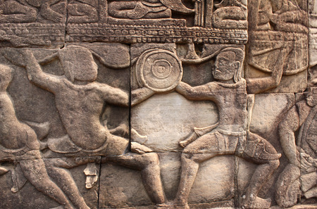 Bas-relief with duel of two warriors, wall in Prasat Bayon Temple, in famous landmark Angkor Wat complex, khmer culture, Siem Reap, Cambodia Stock fotó