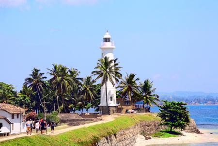 Weißer Leuchtturm und Palmen in Galle Fort. Sonniger Tag. Indischer Ozean, Sri Lanka