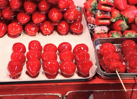 Street food - caramelized red ripe strawberries, street market in Chinatown, Kobe, Japan 스톡 콘텐츠
