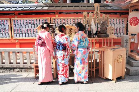 Kyoto, Japan - 3 April, 2019: Three girls in traditional japanese kimono yukata praying at the altar in Kiyomizu-dera Temple (Clean Water Temple)