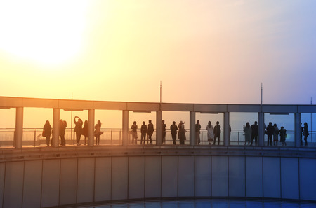 People on the observation deck of Umeda Sky Building, Osaka, Japan. Silhouettes on sunset sky background. Photo toned in orange and blue colors Stock Photo