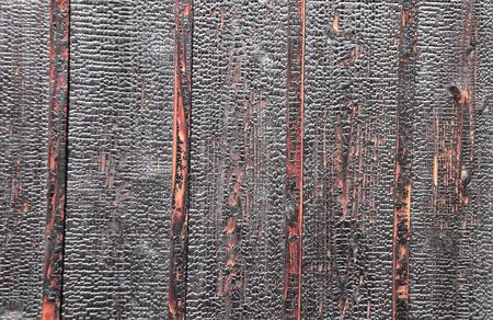 Texture of burnt wooden boards. Damaged burned hardwood surface