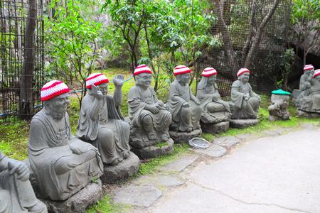 Stone Ksitigarbha statues (Jizo Bosatsu) in a knitted hats, Daishouin (Daishou-in) Buddhist temple, sacred Miyajima Island, Hiroshima prefecture, region Chugoku, Japan Stock Photo