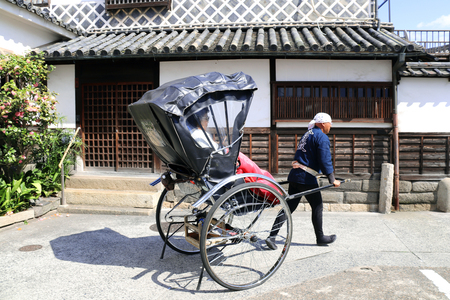 KURASHIKI, JAPAN - 31 March, 2019: Rickshaw on medieval street with traditional japanese houses and storehouses in Bikan district