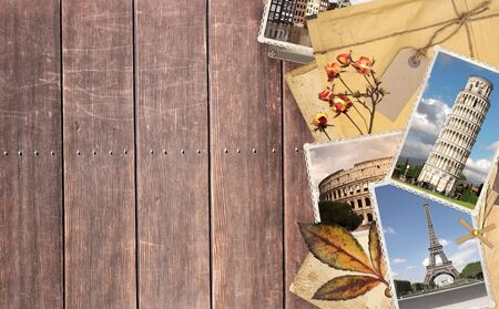 Vintage travel background with old wood planks texture, retro photos of european landmarks, envelope with label, dry rose flowers and leaf. Mock up template. Copy space for text 写真素材