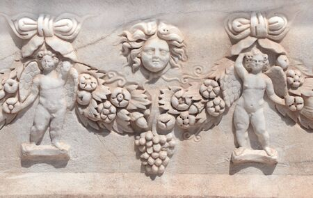 Carved ornament with cupids and a flower garland on a stone sarcophagus, ancient Hierapolis, Pamukkale, Turkey.