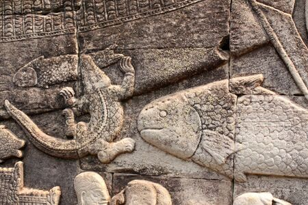 Wall carving bas-relief with animals - crocodile caught a small fish, big fish, Prasat Bayon Temple, in famous landmark Angkor Wat complex, khmer culture, Siem Reap, Cambodia. Imagens