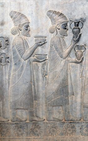 Ancient wall with bas-relief with foreign ambassadors with gifts and donations, Persepolis, Iran. Imagens
