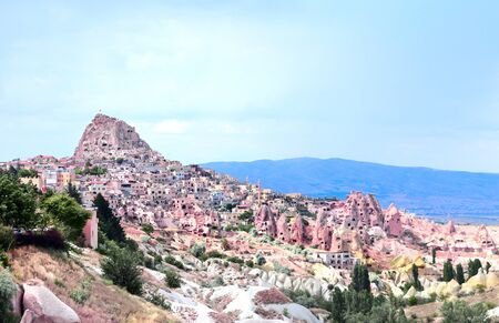 Carved houses in multi-colored rocks in Pigeon Valley, Uchisar, Cappadocia, Turkey Stock Photo