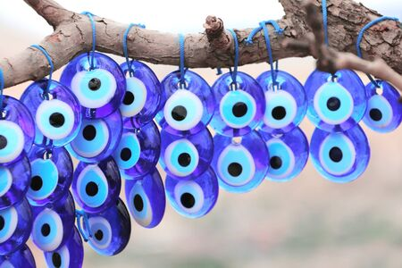 Many glass mascots - evil eye charms hang from a tree in Pigeon valley, Cappadocia,Turkey