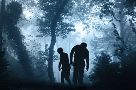 Two zombies in mysterious landscape of foggy forest. Halloween scene with walking dead's. Zombie apocalypse Stock fotó