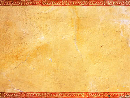 Grunge background with ethnicity ornaments and stucco texture of yellow color. Mock up template. Copy space for text