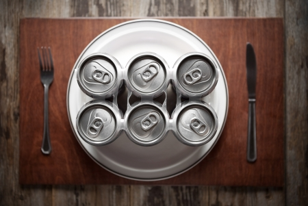 Conceptual image representing alcoholism on a funny way using a six-pack of beer cans for dinner  Archivio Fotografico