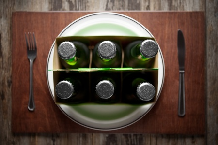 Conceptual image representing alcoholism on a funny way using a six-pack of beer bottles for dinner