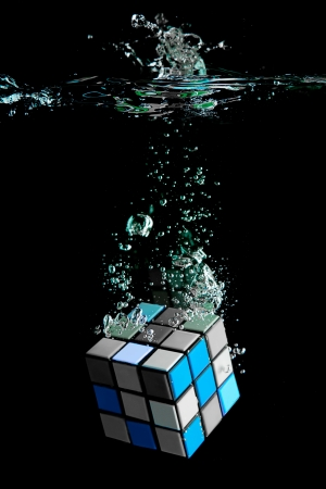 Colorful Blue Cube sinking deep in water and isolated on black background