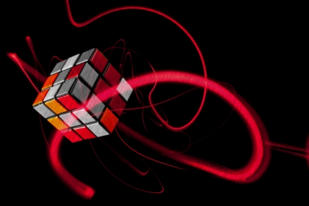 rubik: Colorful Red Cube Floating in the air with light trail and isolated on black Editorial