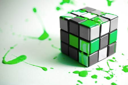 Colorful Green Cube on White surface with Abstract Paint