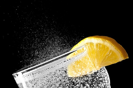 Sparkling water detail with an orange slice isolated on black background