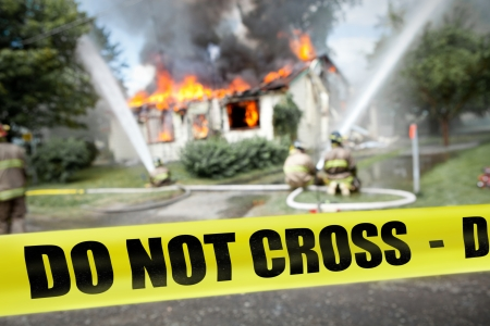Do not cross tape with firefighters and a burning house in the background