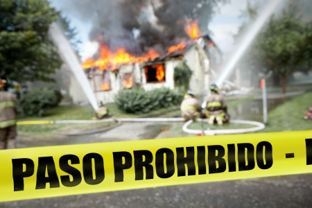 burning house: Spanish  Paso Prohibido  tape with firefighters and a burning house in the background