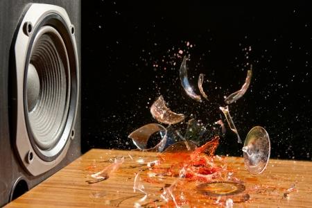 大音量の音楽が引き起こすことができます損傷 - スタジオ ショットのグラスワイン大声でサブウーファーの前で爆発