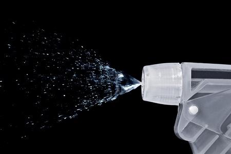gatillo: Macro de una botella de boquilla de pulverización de agua sobre fondo negro