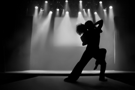Couple in silhouette dancing on a stage