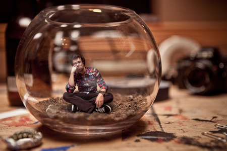 Unhappy Miniature Waiting Man Trapped inside a Fishbowl. photo