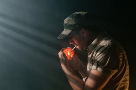 Young Addicted Adult lighting a marijuana Joint in the dark Standard-Bild