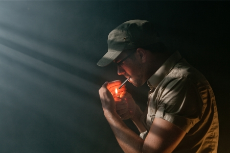 Young Addicted Adult lighting a marijuana Joint in the dark photo