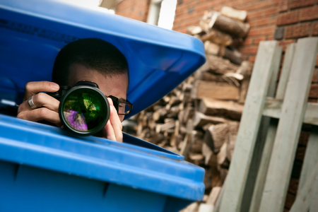 Paparazzi hiding in a blue garbage bin to take pictures photo