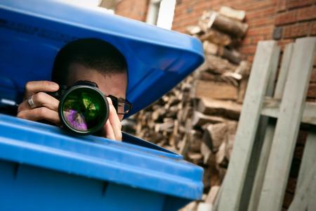 Paparazzi verstopt in een blauwe vuilnisbak om foto's te maken