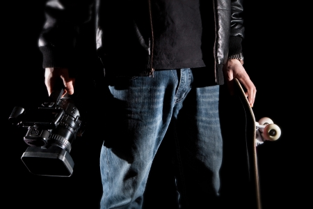 video camera: Skateboarder Holding a video camera and a skateboard isolated on black background