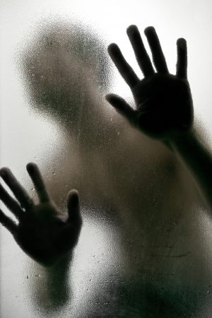 Dark Silhouette of a man with hands on a frosted glass Stock Photo