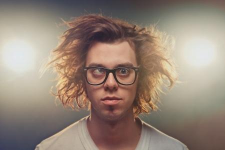 백그라운드에서 스포트 라이트를 사용하여 스튜디오에서 헝클어 진 갈색 머리와 함께 재미 가늘게 뜨고 사람