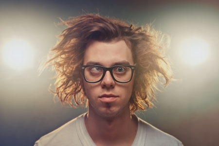 Funny Squinting man with Tousled brown hair in studio using spotlights in background Stok Fotoğraf