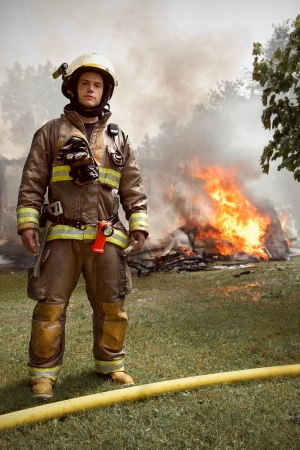 Real People - Firefighter Portrait with house on fire in background Archivio Fotografico