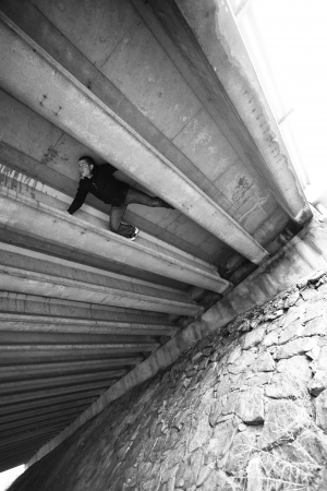 Black and White image of Man doing some crazy Parkour under a bridge structure